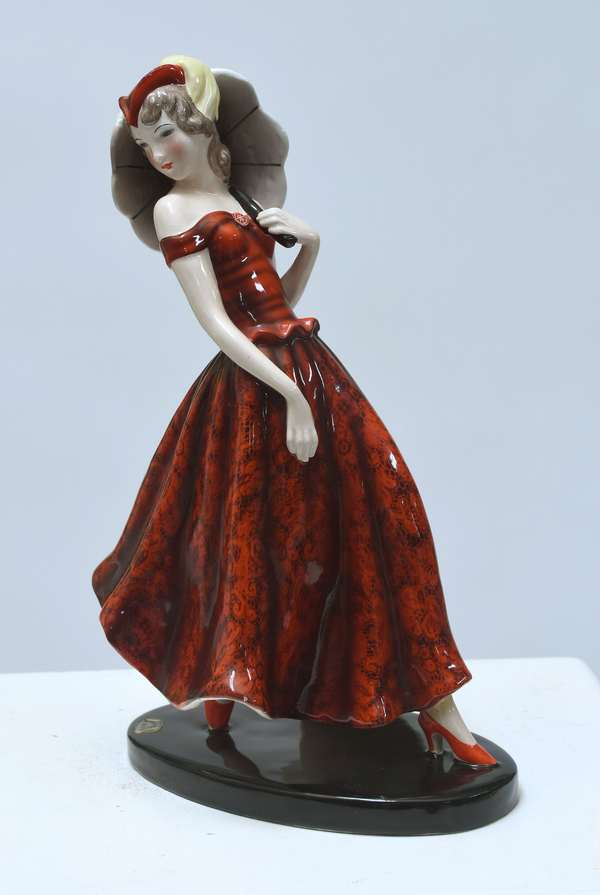 """Goldscheider Art Deco figure of woman in patterned red dress, with parasol, 12""""H.  Retains original paper label. Marked Made in Austria, impressed 7390-76-10, black artist monogram, ca.1930."""
