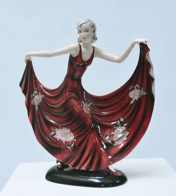 """Goldscheider Art Deco figure of dancing woman in outstretched red dress with floral pattern, impressed """"Goldscheider Wien, Made in Austria- Dakon"""", 7961-35-19. 13.5""""H. x 12.5""""W., ca.1930."""