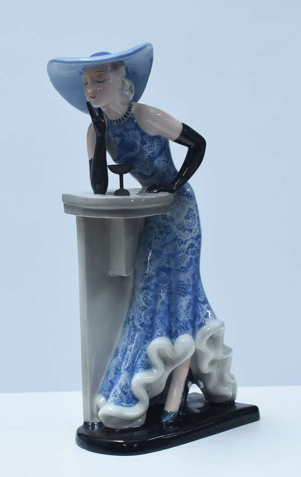 """Goldscheider figure of Art Deco woman in blue hat, blue patterned dress, and black gloves, with martini glass on the bar.  Marked """"Goldscheider Wien, made in Germany, impressed 7509-279-19, ca.1930-35, 12.5""""H."""