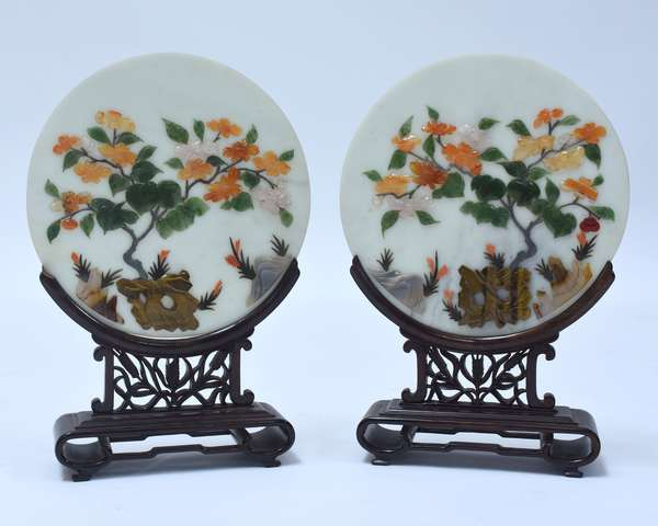 """Good pair of Chinese hardstone table screens, round stone plaque with jade, carnelian, rose quartz, tigers eye, agate, and other materials. Plaques sit in carved rosewood frames, 10.75""""Dia., 16""""H. overall, Republic period."""