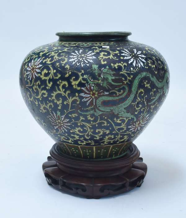 """Large Chinese 19th C. enamel decorated jar, 16""""H. x 21""""Dia. with flying dragon and floral motif, in colors of yellow, green, rust, and blue, very dramatic on carved rosewood base"""