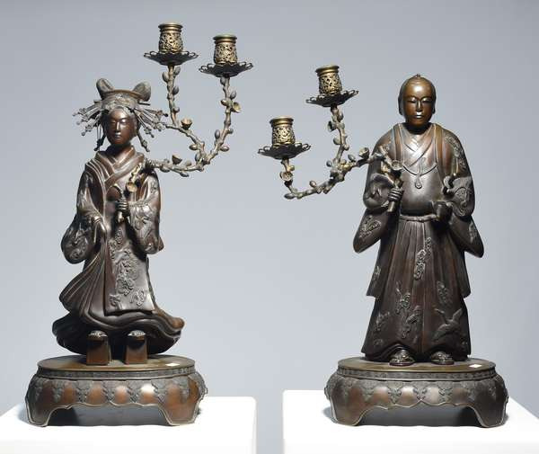 """Pair of Meiji period Japanese figural candelabras, Samurai with swords and Geisha with multiple hair combs, both figures hold cherry tree branches forming double candelabra, 23""""H., reddish brown patina, appear unsigned."""