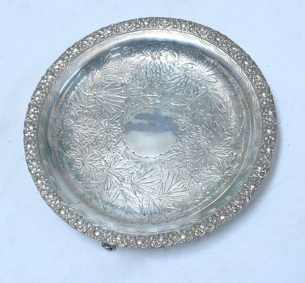 """Tiffany & Co Makers sterling footed tray, 10"""" Dia. with repoussé border and chased floral center, ca.1873-1891, approx. 22 troy ozs"""