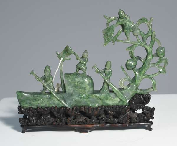"""Chinese Republic period carved jade boat with figures on interior, carved rosewood base resembles waves. Jade 5.5""""H. x 8.5""""L., 7""""H. overall."""