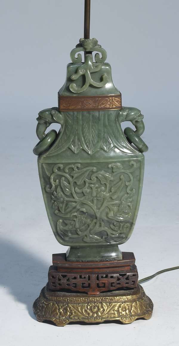"""Large Chinese jade urn converted to lamp with carved handles and finial, front and back carved with fish, vines, floral, foo dogs. Carved rosewood base inlayed with silver wire. Jade bangle forms finial to lamp. Urn 15""""H."""