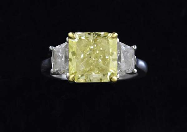 Stunning 3 stone diamond ring, center stone with GIA cert, 4.24 ct. cut corner square modified brilliant, color-fancy yellow, clarity VS1, report number 1112295150, flanked with 2 trapezoid cut diamonds approx. 1ctw, set in 18k and platinum, size 6-6.25