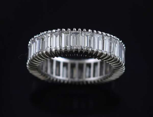 Platinum emerald cut diamond eternity band set with approx. 8.0 ct. tw. baguettes, 6 mm, sz. 6 1/4, 6.8 grams.