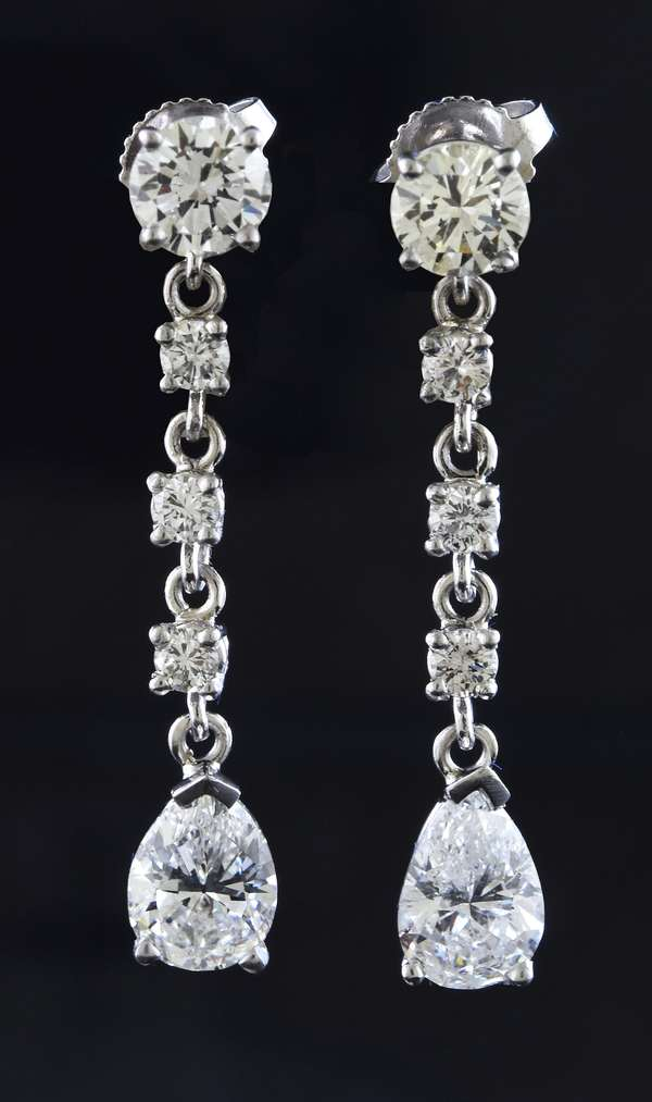"Pair of diamond dangle earrings with (2) 1.03 and 1.05 pear shaped dia. drops accented by approx. 1.40 ctw of other diamonds, 1.25""L., 4.9 grams"