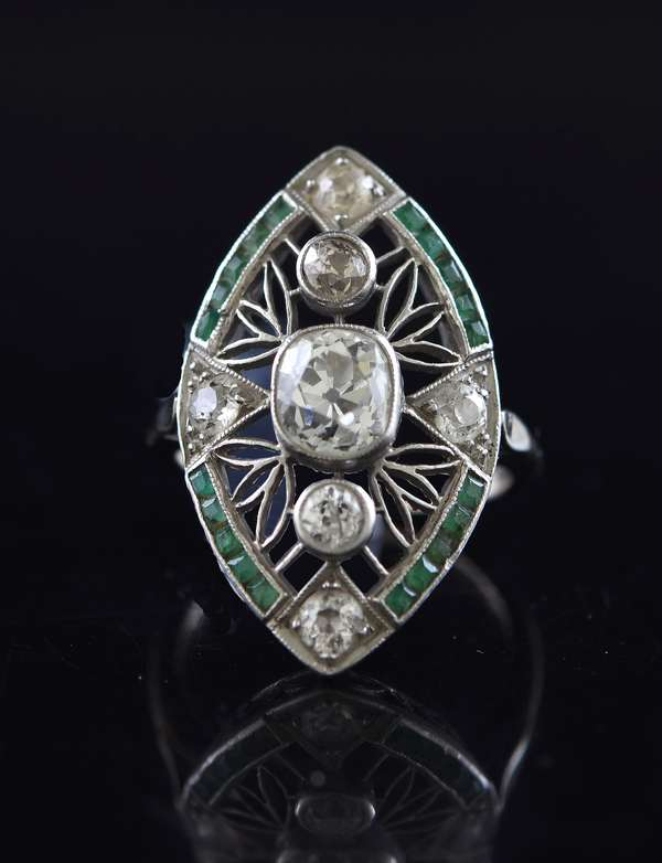 Tested 14k white gold navette ring set with an approx. .95 ct old mine cut, .60 ctw old European cut stones accented by .30 ctw calibre cut emeralds, size 4.75, 4.9 grams