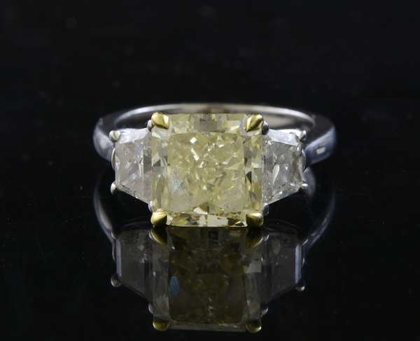 Stunning 3 stone diamond ring, center stone with GIA cert, 4.24 ct. cut corner square modified brilliant, color-fancy yellow, clarity VS1, report number 1112295150, flanked with 2 trapezoid cut diamonds approx. 1ctw, set in 18k and platinum, size 6-6.25, 7.7 grams
