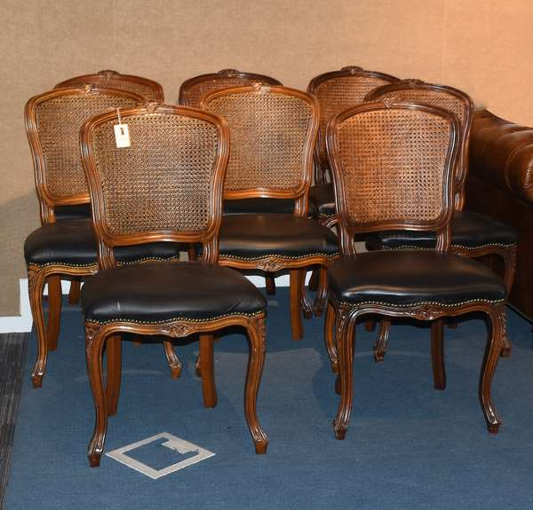 Set of eight French style caned back dining chairs with black leather upholstered seats