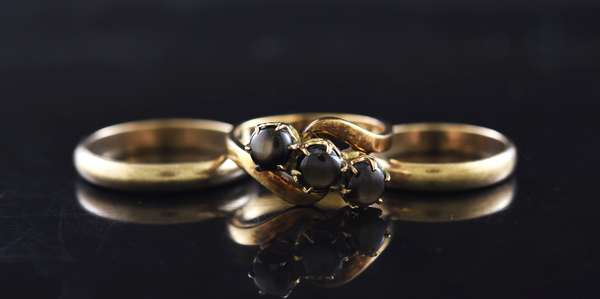 Three rings stamped 333 or 8kt yellow gold: Gents wedding band, 4 mm, 3.7 gr. Ladies wedding band, 4 mm, 2.6 gr. Three, 6 mm black star sapphire ring, 3.7 gr. (875-53)