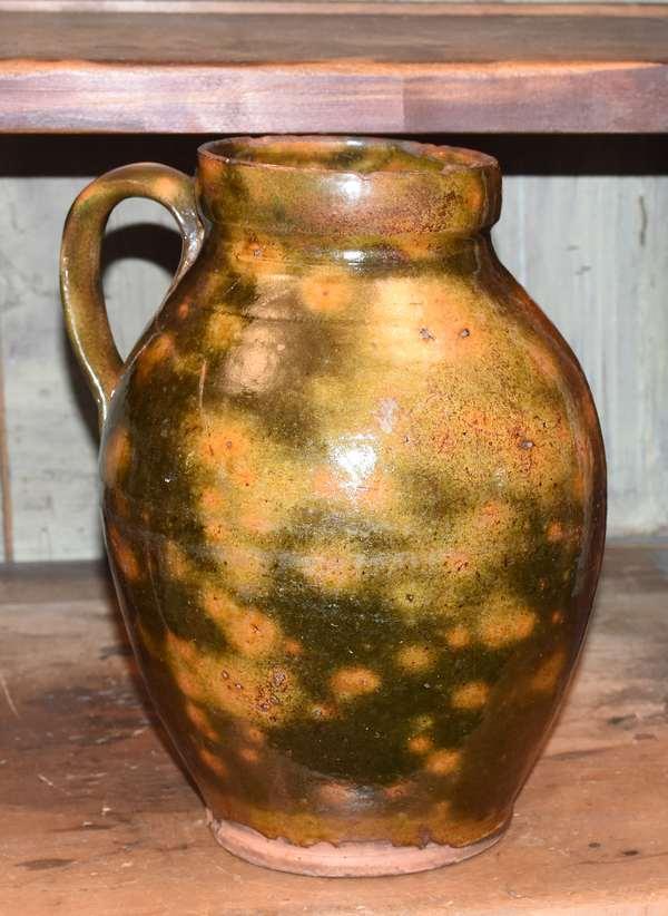 "Slip decorated 19th C. redware handled jug, 10.5""H."