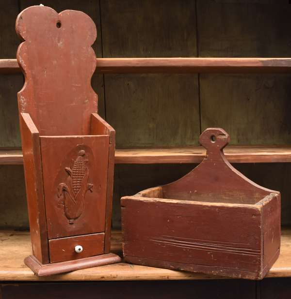 """Two early wall boxes, one drawer red painted candle box with corn carving 28""""H. with a lollipop handle wall box in red, 15""""H."""