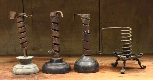 Four early wood and iron spring candle holders