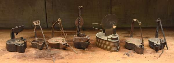 Seven early iron and tin Betty lamps
