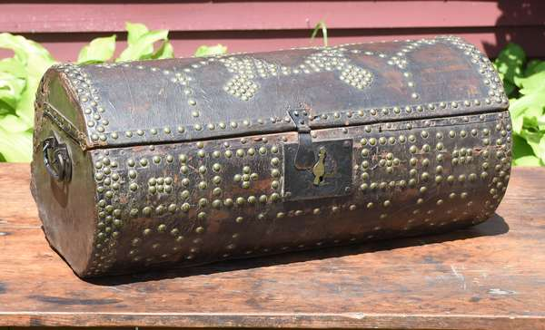 """19th C. brass studded leather covered trunk in barrel form with label Daniel Gladding New Haven dated 1809, 24""""L. x 10""""H."""