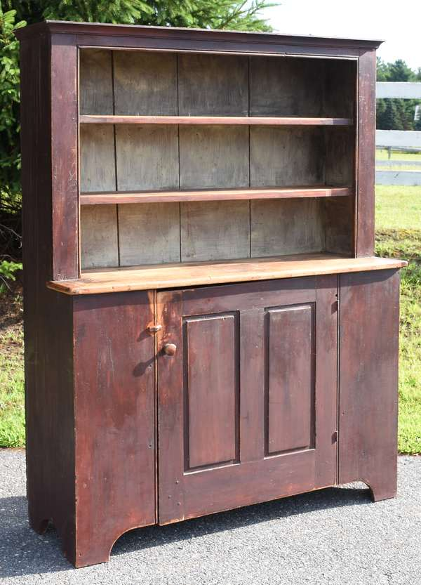 """Country set back cupboard in old red paint with molded crest, raised paneled door, and a cut out base 54""""W. x 75""""H. x 19""""D."""