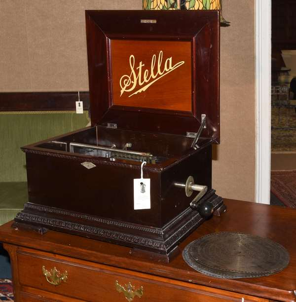 """Stella 9.5-inch disc music box in carved mahogany case, No. 24801, with three discs, 16""""L. x 13""""W."""