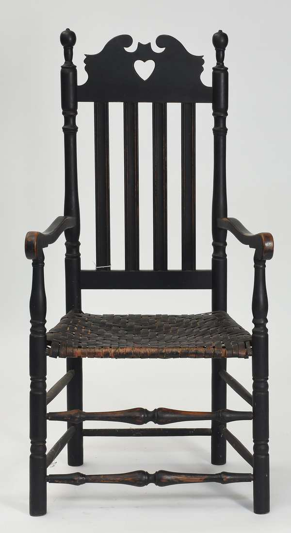 """18th C. bannister back armchair in black paint with heart and crown motif, double stretcher and splint seat, 17""""H. seat height, 47"""" overall, Prov. The estate of Roland Barnard"""