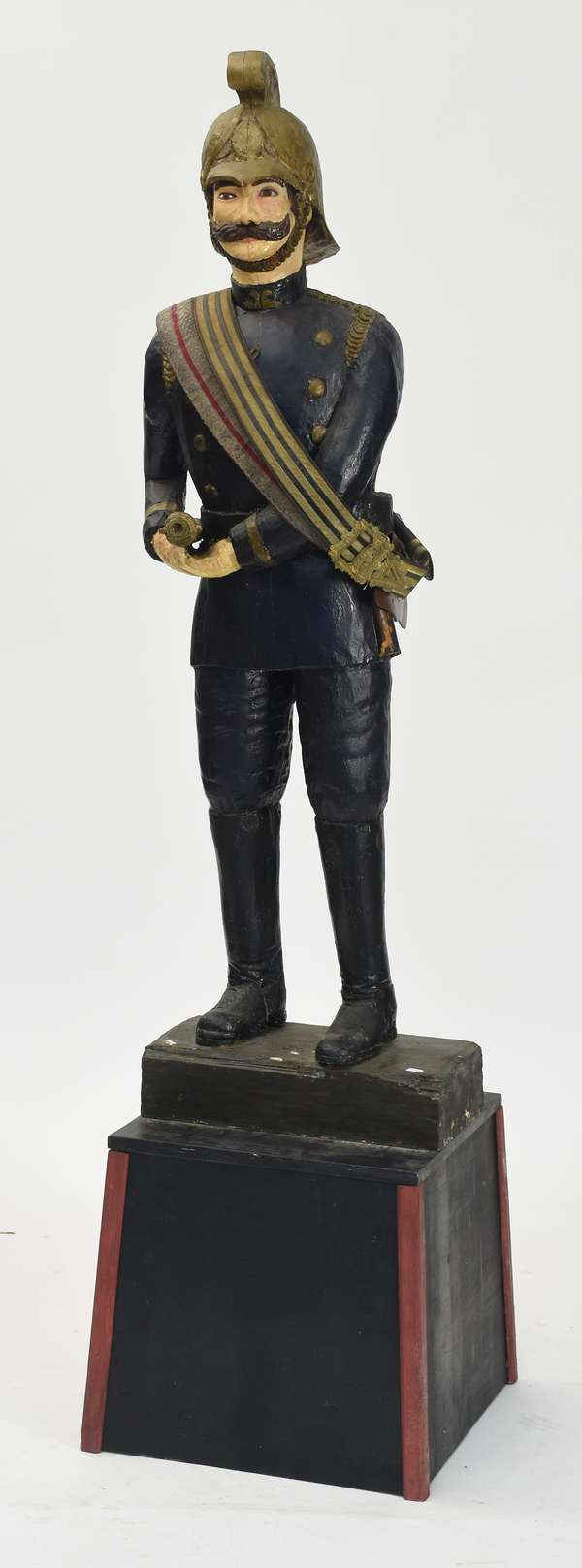 """Early carved and painted wooden firefighter figure holding a fire nozel with an ax at his side, on base, 70""""H."""