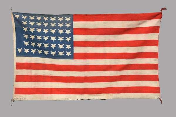 """Important forty-four star Germantown pictorial flag weaving, ca. 1890-1895, 30"""" x 51"""". Made soon after Wyoming's entrance to union on July 10th, 1890, and has a unique configuration of 44 inverted stars. Illustrated in """"Navajo Pictorial Weavings, 1880-1950"""" by Tyrone Campbell and Joel and Kate Kopp, 1991, pg 74. One of the earliest Germantown flag weavings known."""