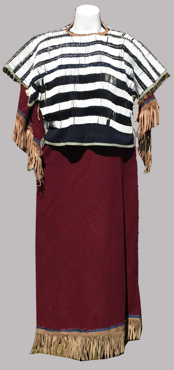 Exquisite Sioux maroon wool trade cloth dress with black and white bugle beaded yoke and Arabic coin fringe, hide ties, ca. 1880-1900