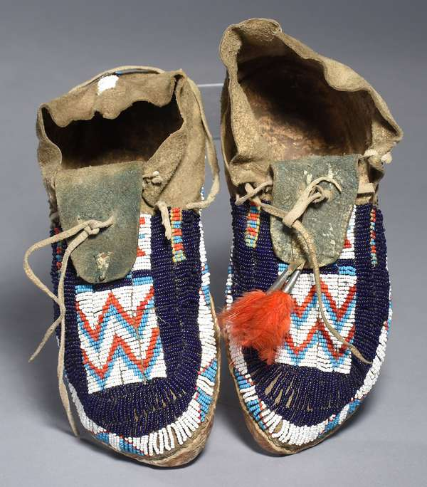 """Arapahoe ladies fully-beaded sinew-sewn moccasins, one with red feather decoration, with navy, white, turquoise, and red beading, ca. 1890, 10""""L."""