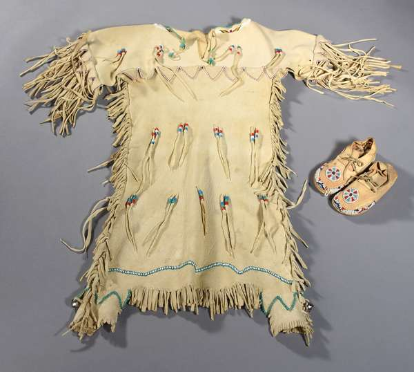 """Small child's buckskin dress with beading, cowrie shells, brass beads, bells, and fringe, with a blue beaded neckline, 1930s/40s, 29""""H. (original museum collection), along with a pair of small child's beaded moccasins, 5.5""""L."""
