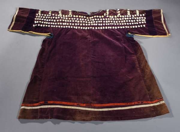 """Sioux child's purple velvet dress with cowrie shell yoke decoration, and silk ribbon edging, ca. 1860-1890, 28""""H. x 34""""W. Similar to those sold by the Otto Ernst Saddlery in Sheridan, Wyoming in the 19th century, where Mr. Ernst would purchase items from Native Americans and sell them in his shop and catalog."""