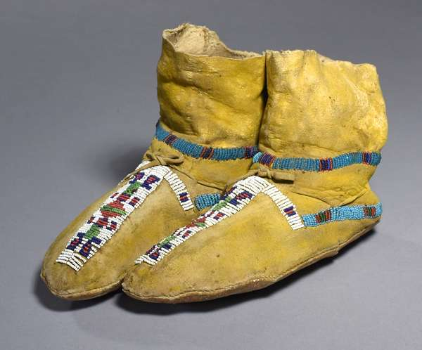"""Southern Cheyenne high top moccasins with yellow ochre painting, partially beaded, sinew sewn, 9""""L."""