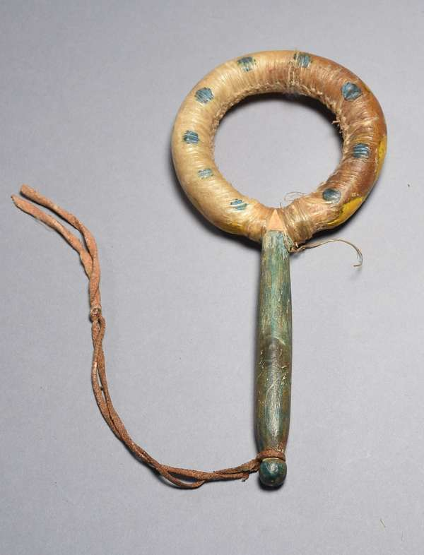 """Circular Plains Ghost Dance rattle, parfleche with sinew sewing and rawhide, green and yellow paint, ca. 1890-1900, 7""""L."""