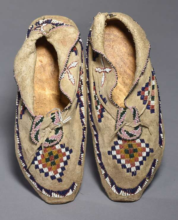 """Cheyenne ladies partially beaded moccasins, with beaded edgework, round beaded tongue, and red, white, blue, pink, green, brown, white beading, 10""""L."""