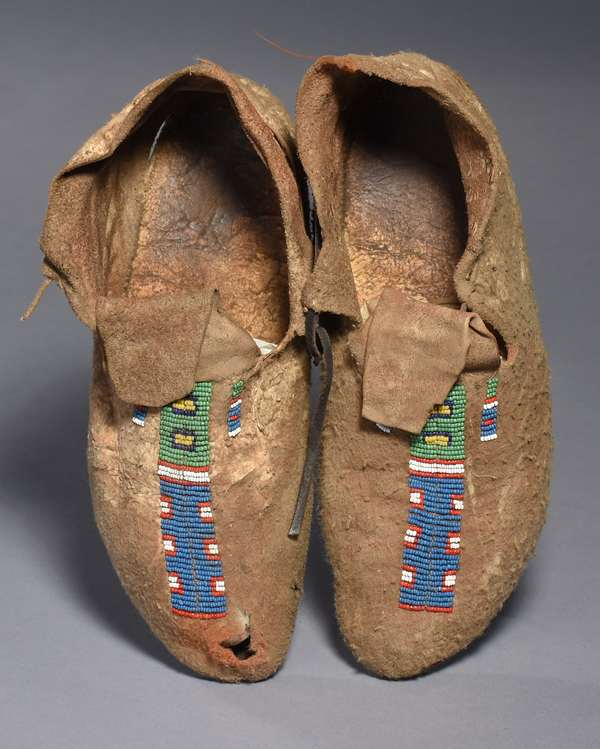 """Plains partially-beaded brain-tanned moccasins, with full soles; green, red, yellow, blue and white beads, 1880-1900, 11""""L."""