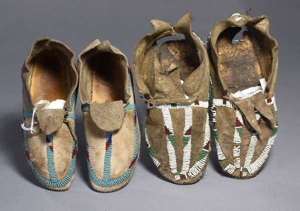 """Two pairs of partially beaded children's Plains moccasins, one with damage, both 7.5""""L."""