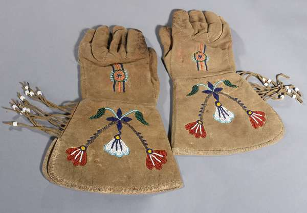 """Pair of Plains gauntlets with fringe and beaded decoration, lined with fabric, mid-19th C., 12""""H."""