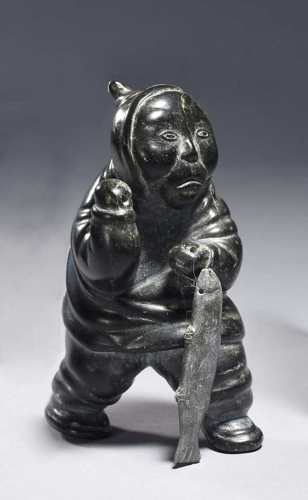 """Inuit carved soapstone figurine, man with fish, 1940s/50s, finely carved with good patina, 6.5""""H. x 4.5""""W."""