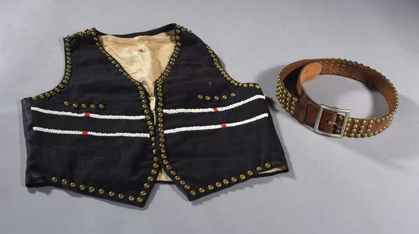"""Crow reservation vest, turn-of-the-century, black silk and wool, with brass tacks and beading, along with a Blackfoot reservation belt, leather with brass studs, 35""""L"""