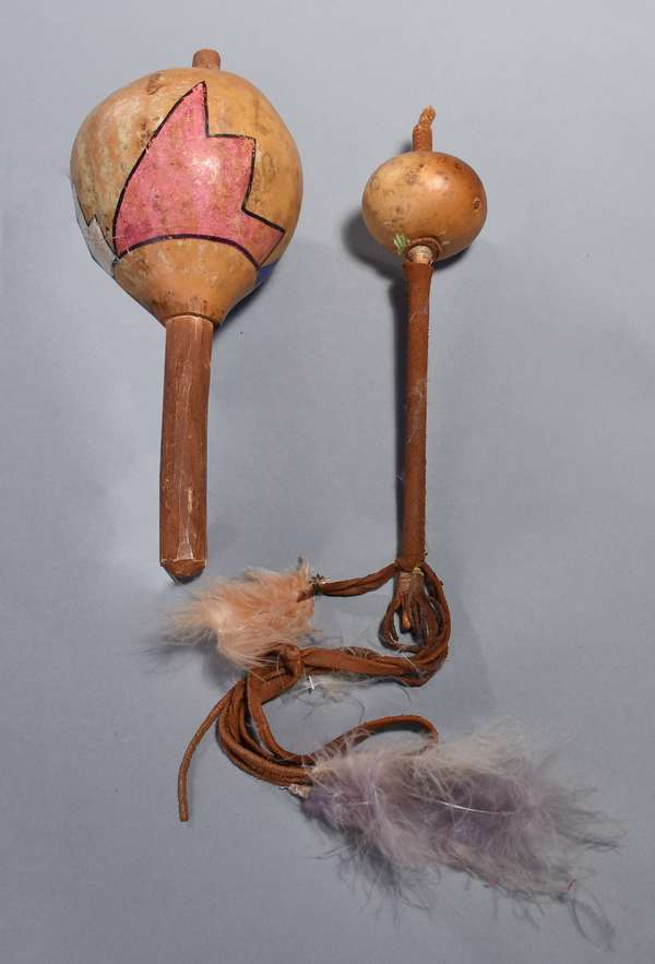 """Two rattles: Hopi gourd second rattle Peyote      with painted decoration in white, pink, and blue, 11""""H, with a smaller rattle, hide wrapped, with hide and feather fringe, 11.5""""H"""