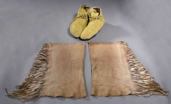 """Pueblo yellow ochre painted moccasins, with blue painted edging, and rolled rawhide soles, 1940s, 11""""L.; with a pair of Plains hide leggings with fringe, 1920s, 15""""L."""