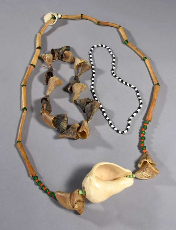 """Klamath necklace with bone, red and green greasy beads, dewclaw and shell ornamentation, 52""""L.; along with a dewclaw necklace, 26""""L., and a black and white pony bead necklace, 20""""L."""