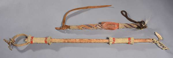 """Two quirts: Mojave example with red-dyed horse hair and woven fibers; with a hide covered example with beading and wrist strap, 24""""L."""