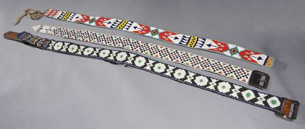 """Three beadwork belts: loomed beadwork belt with checker pattern, 34""""L.; leather belt with loomed beadwork covering, 42""""L.; and a hide belt with beadwork decoration, 36""""L."""