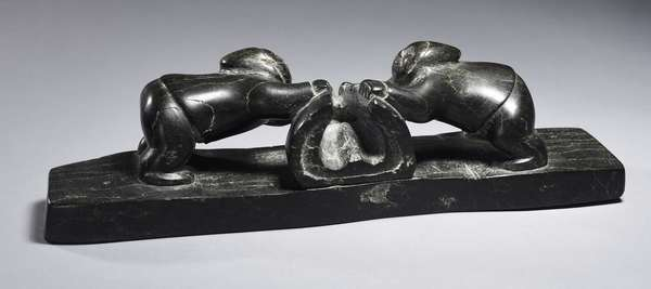 """Large unusual Inuit caved soapstone sculpture, two figures harvesting seal carcass, 1940s/50s, 13.5""""L. x 3.5""""W. x 3.5""""H."""