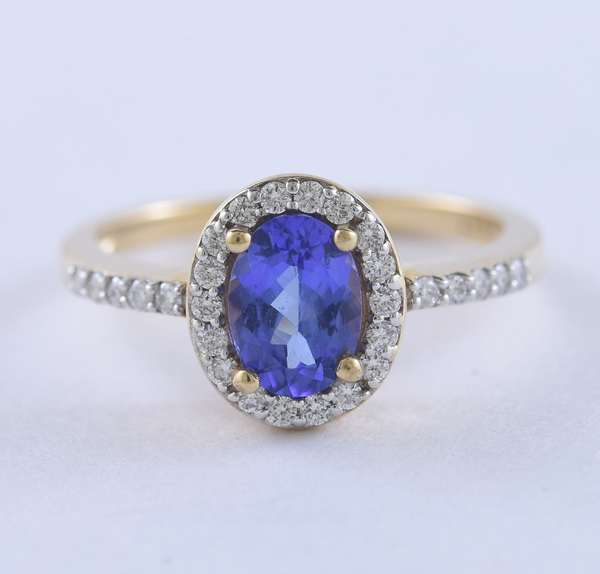 Lady's 10kt yellow gold oval tanzanite (.85 ctw) and diamond ring, approx. .30 ctw diamonds surrounding the stone and on the shoulder, size 7, 2.79 grams