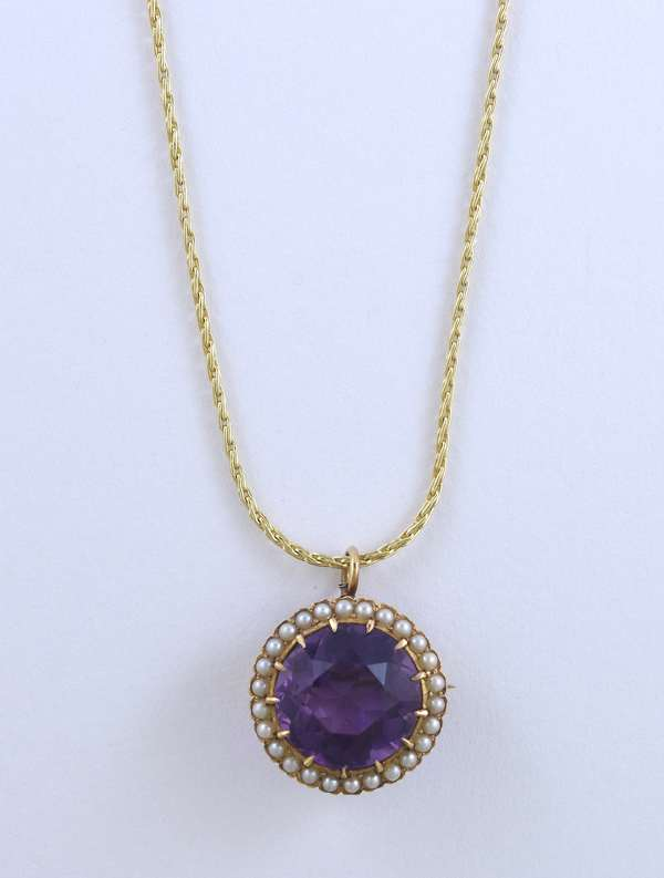 14kt yellow gold amethyst pin/pendant approx. 5 ct. round surrounded by seed pearls, 18 in. long, 10 gr.