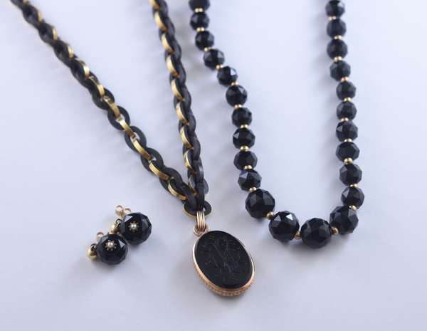 Three items: Victorian mourning necklace with 14kt rose gold (tested) engraved monogram pendant, 1 in., and carved Gutta Percha chain wrapped in 14kt yellow gold (tested), clasp is not gold, 21 in. long and a graduated strand of faceted black beads, 9-12 mm, 15 1/2 in. with matching post earrings with 14kt yellow gold findings and pearl accents.