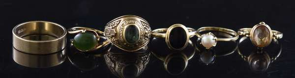 Six 10kt gold rings: class ring, oval onyx, nephrite jade, pearl, citrine and 7 mm band, 18.7 grams.