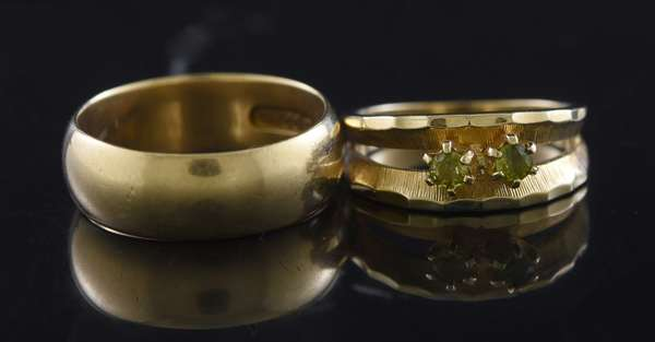 Two 14kt yellow gold rings: 7 mm half round band, sz 8 3/4, mother's ring w/ two peridot, sz. 7, 11.6 grams.