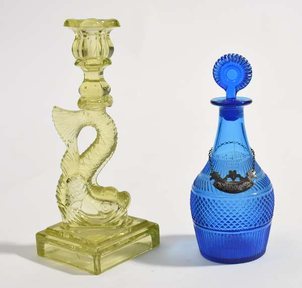 """19th C. Colored vaseline dolphin form candlestick, 10.5""""H., with an early blue glass decanter, 8""""H."""
